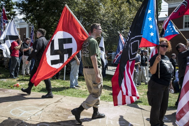 A white nationalist carries a Nazi flag during a protest in Charlottesville, Va.